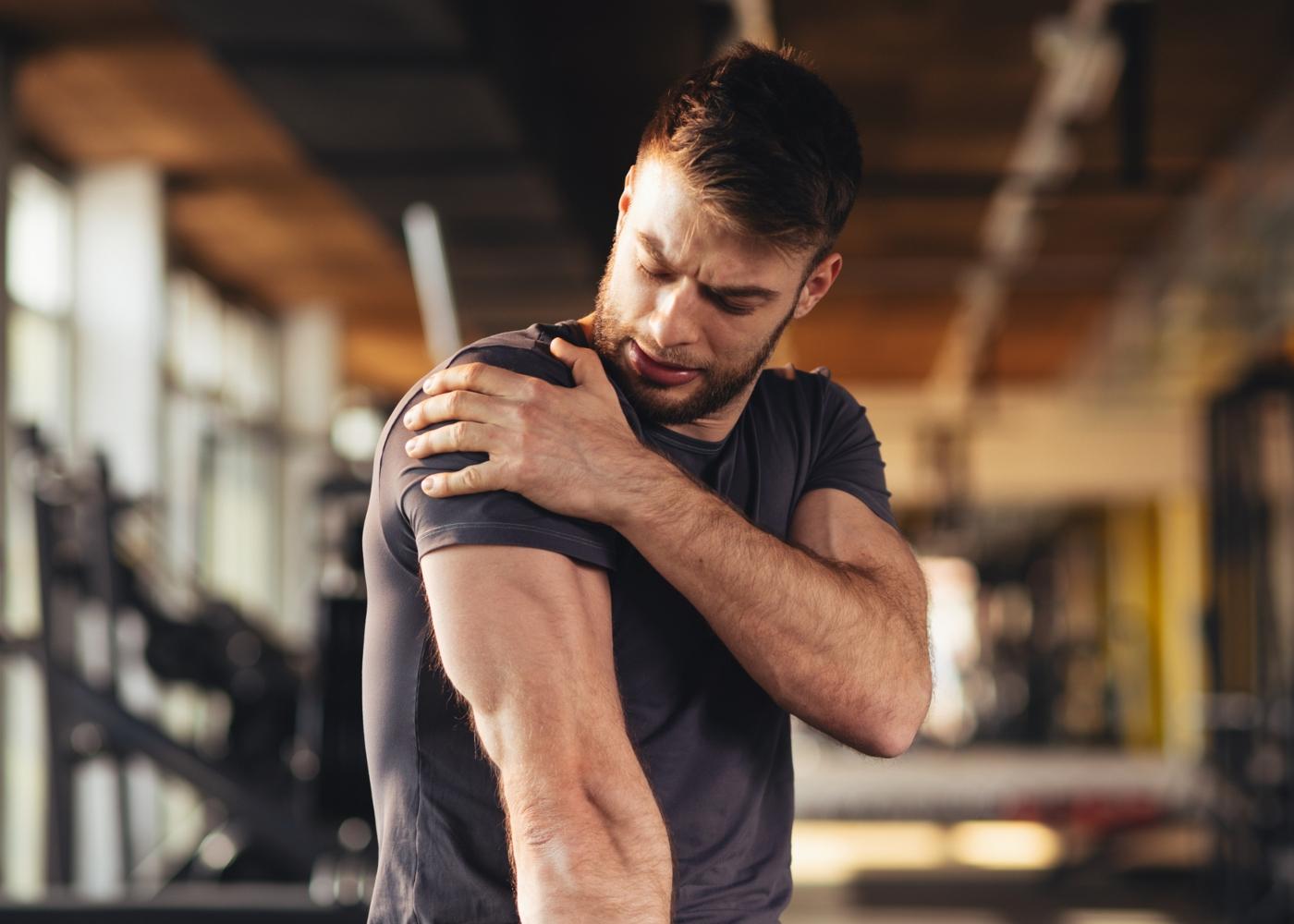 Homem no ginásio com dor no ombro