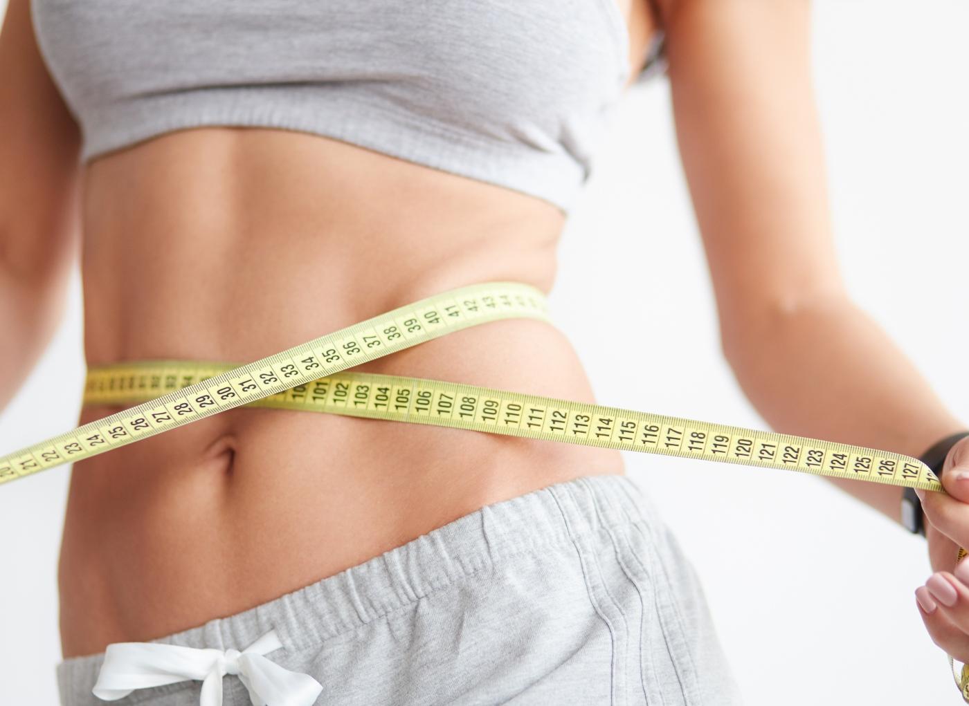 Mulher a verificar medidas tendo em vista o cálculo do peso ideal