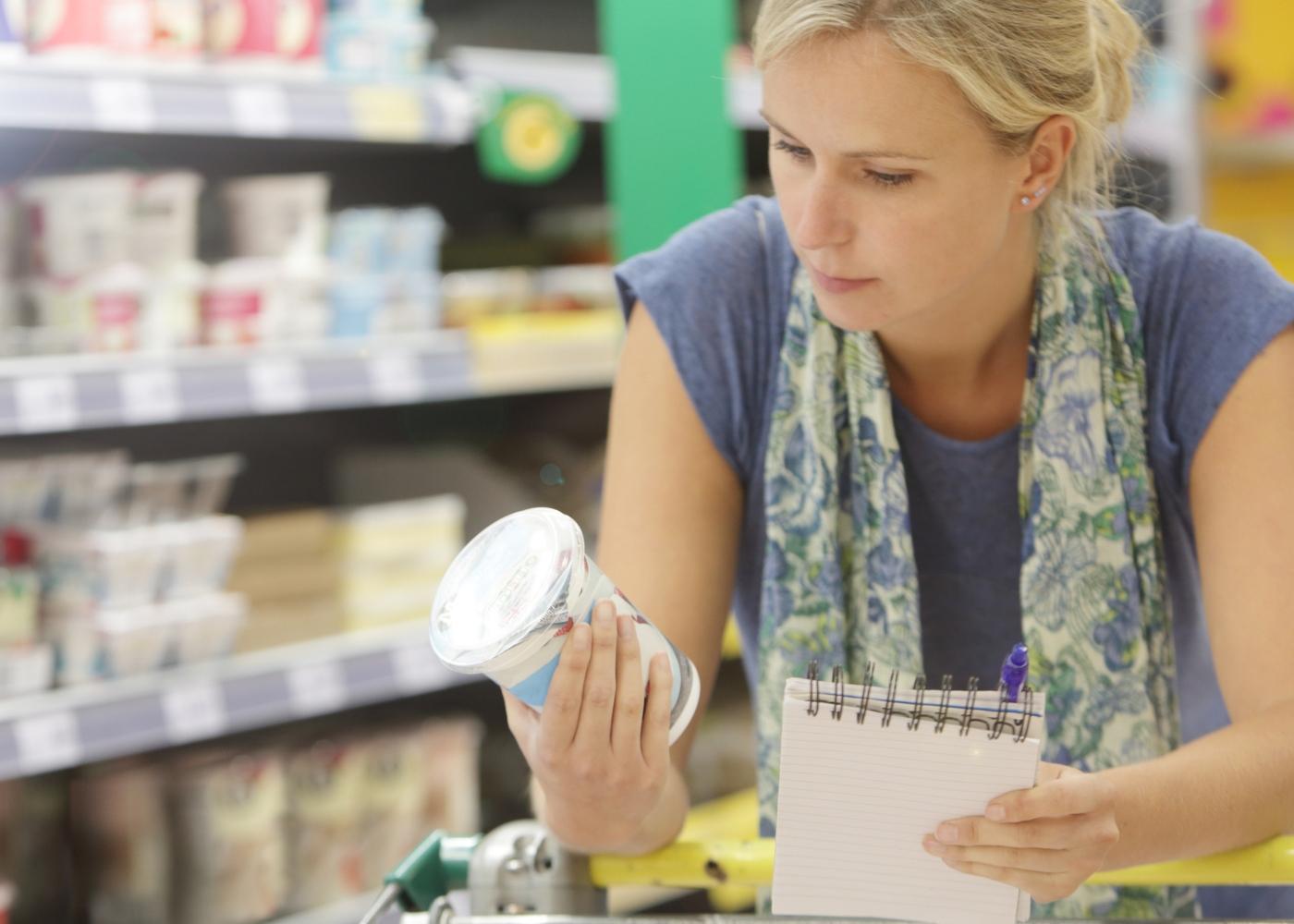Mulher a ler informação nutricional de alimento no supermercado