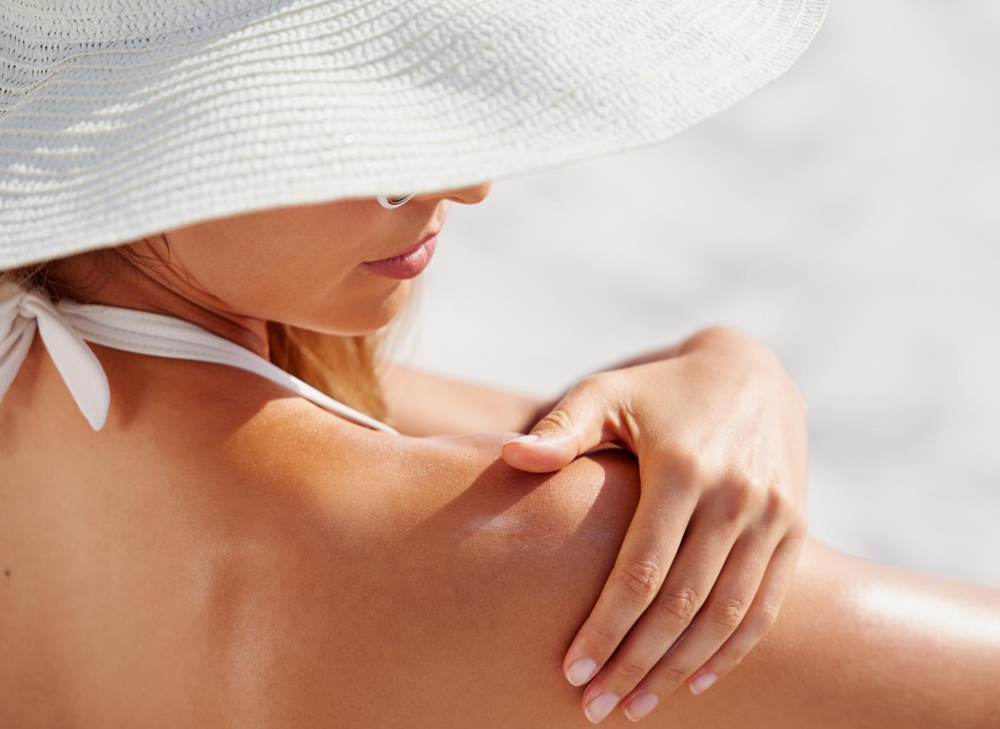 Mulher a aplicar protetor solar