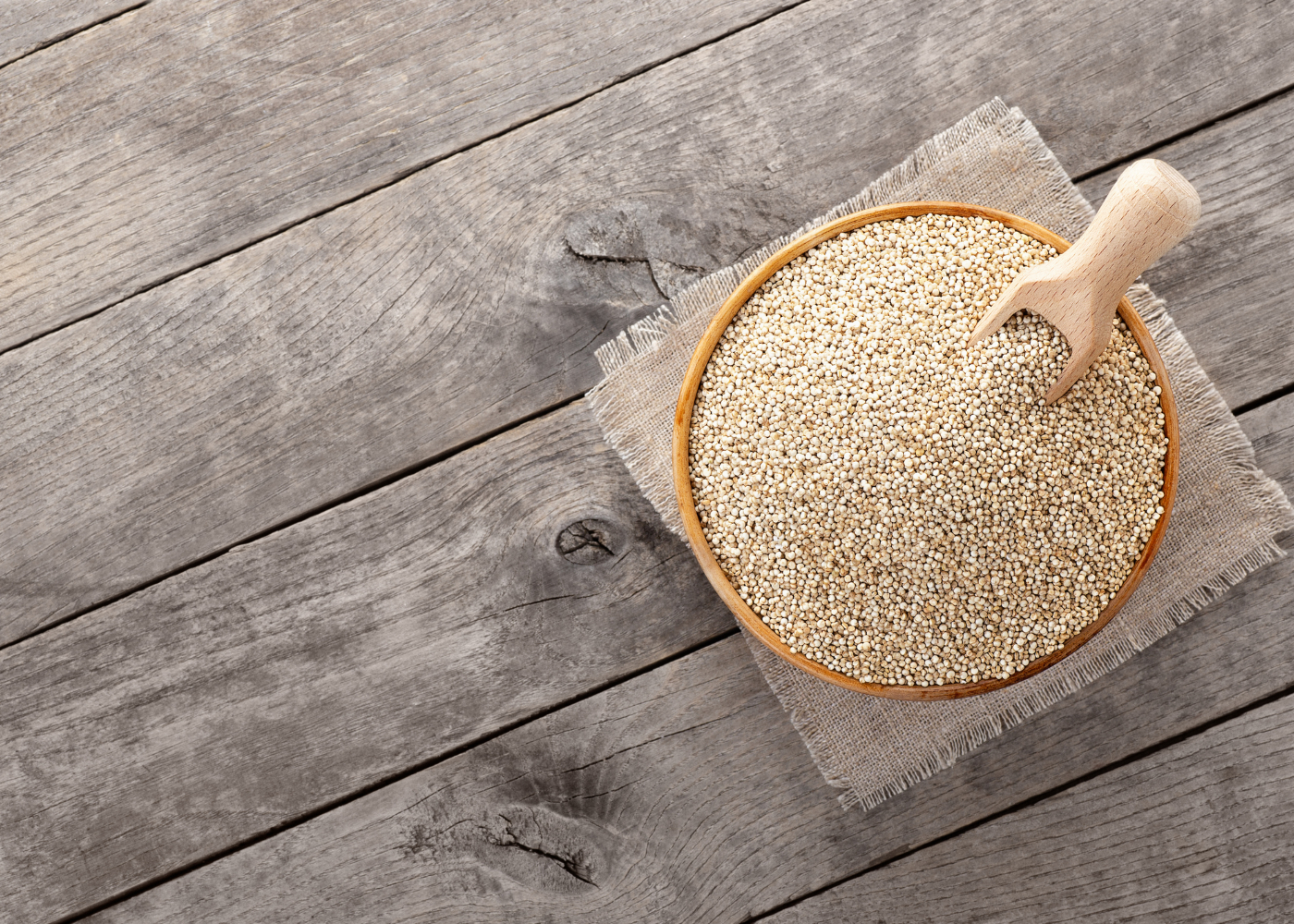 Taça com quinoa em cima de mesa de madeira