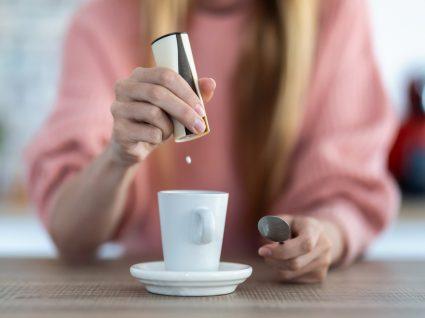 mulher a colocar adoçantes artificiais no café