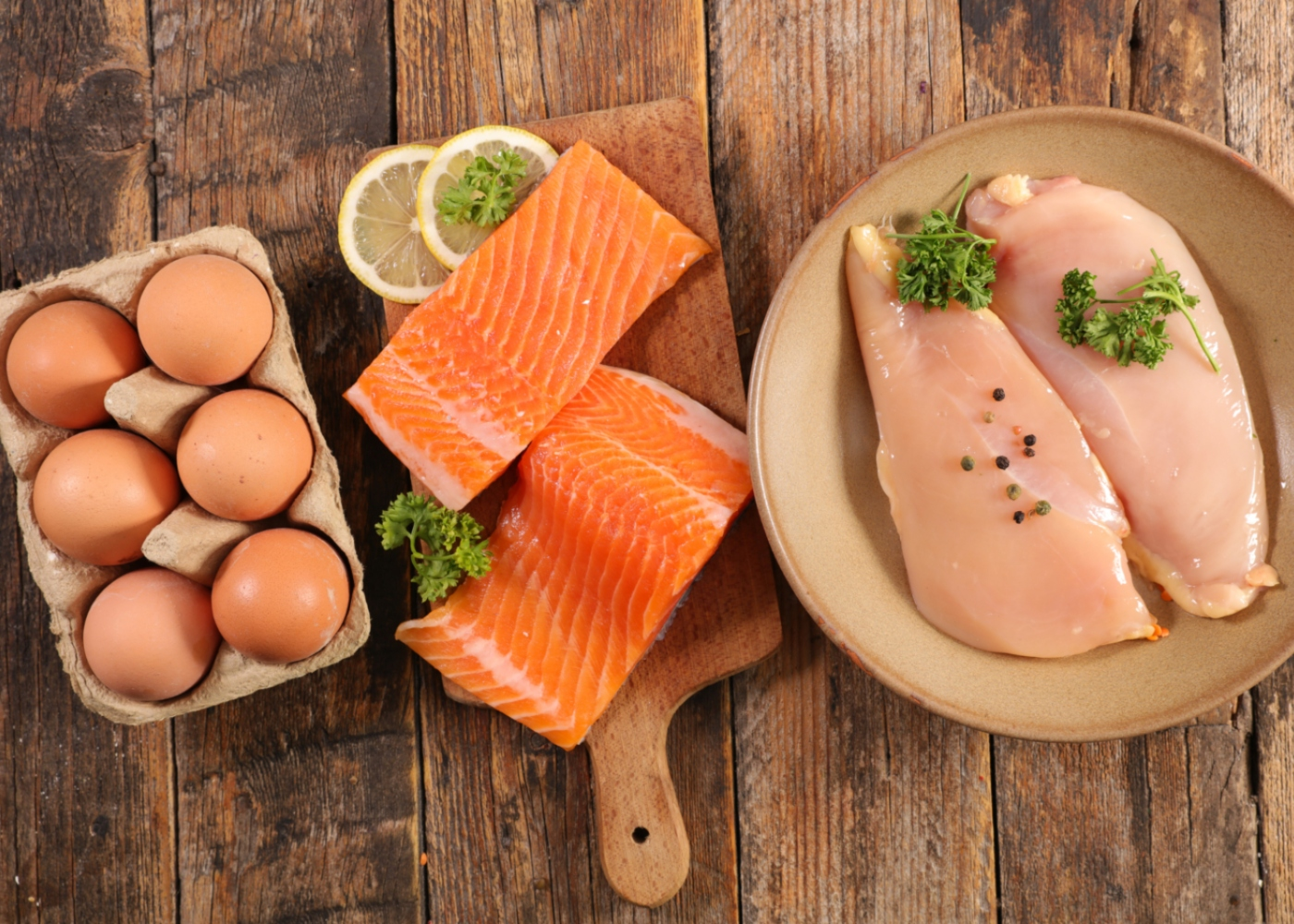 Carne, peixe e ovos em cima de mesa de madeira