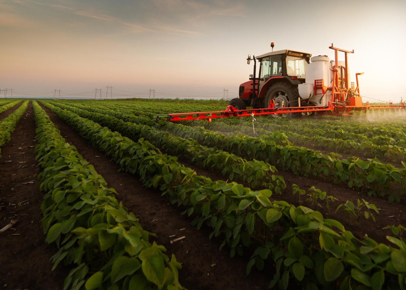 Trator a regar campo agrícola