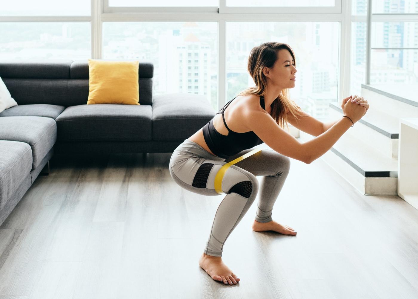 Exercícios de glúteos para fazer em casa: mulher a fazer agachamentos
