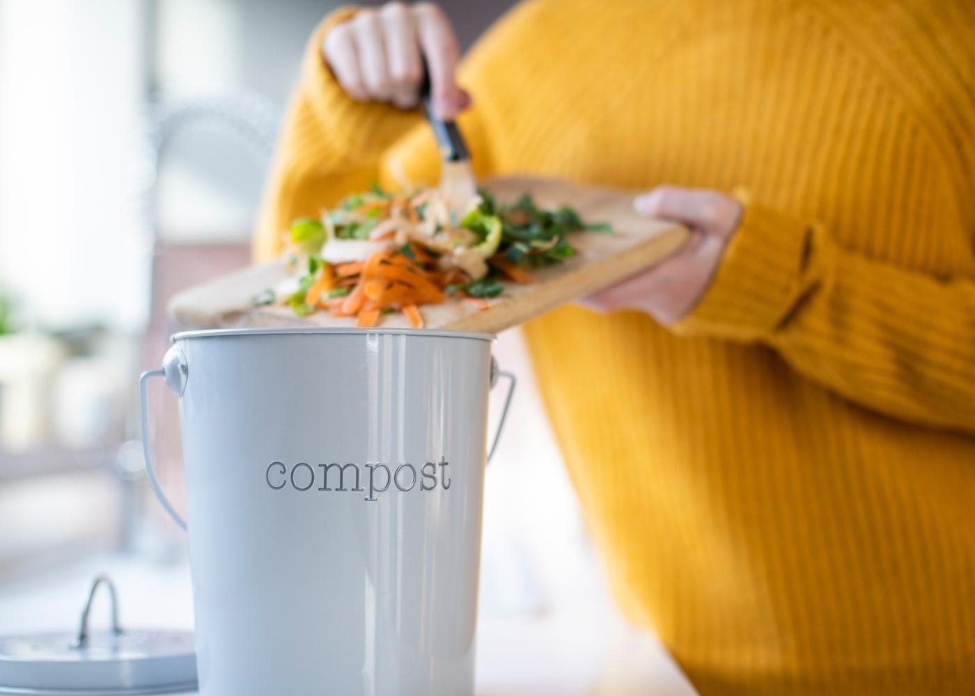 Mulher a separar sobras de alimentos para a compostagem