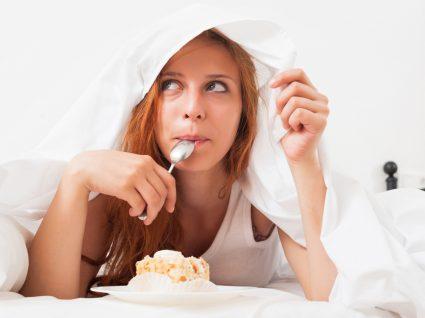 Fome emocional: mulher a comer doces em casa