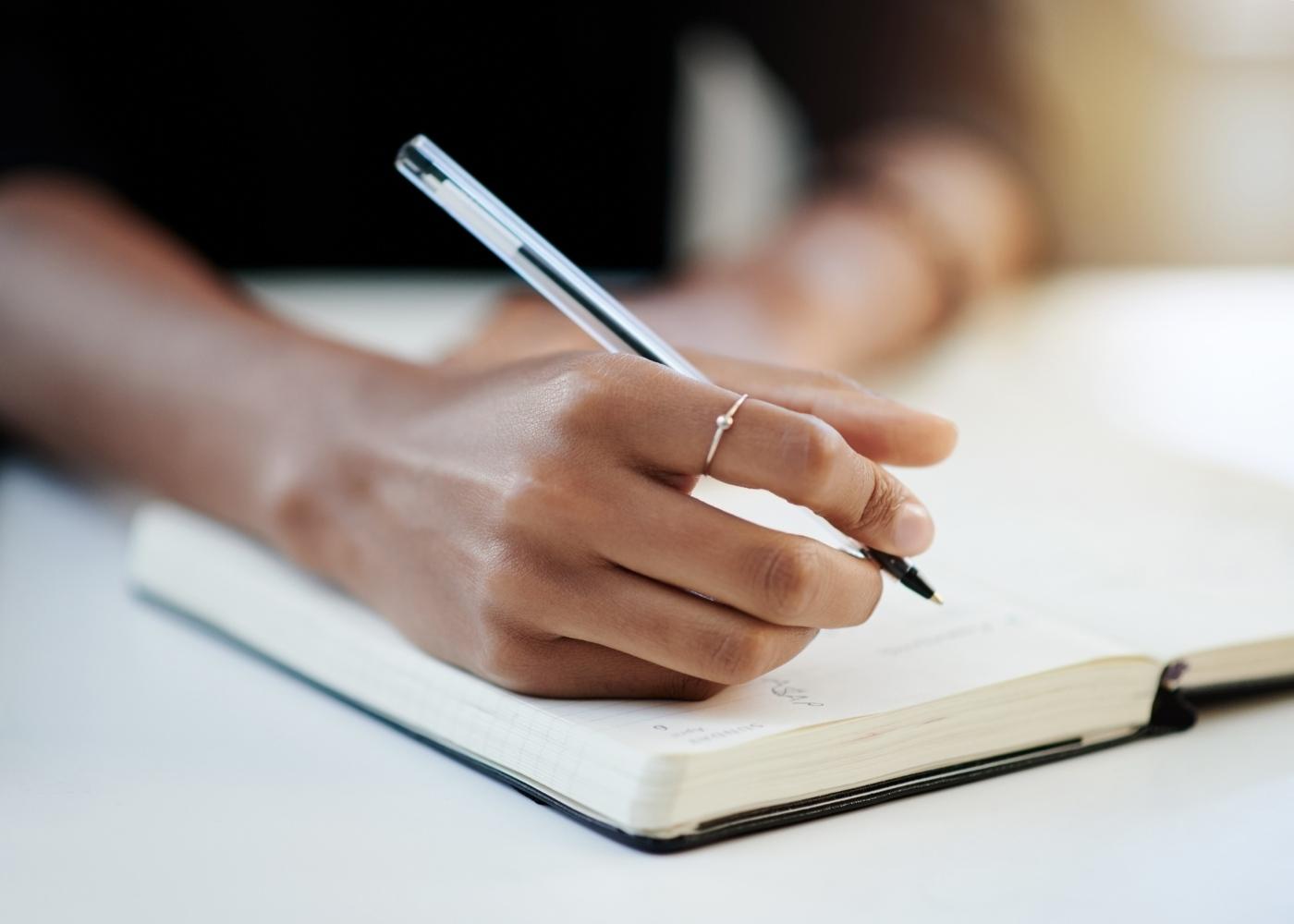 Mulher a registar num caderno os momentos em que sente fome emocional