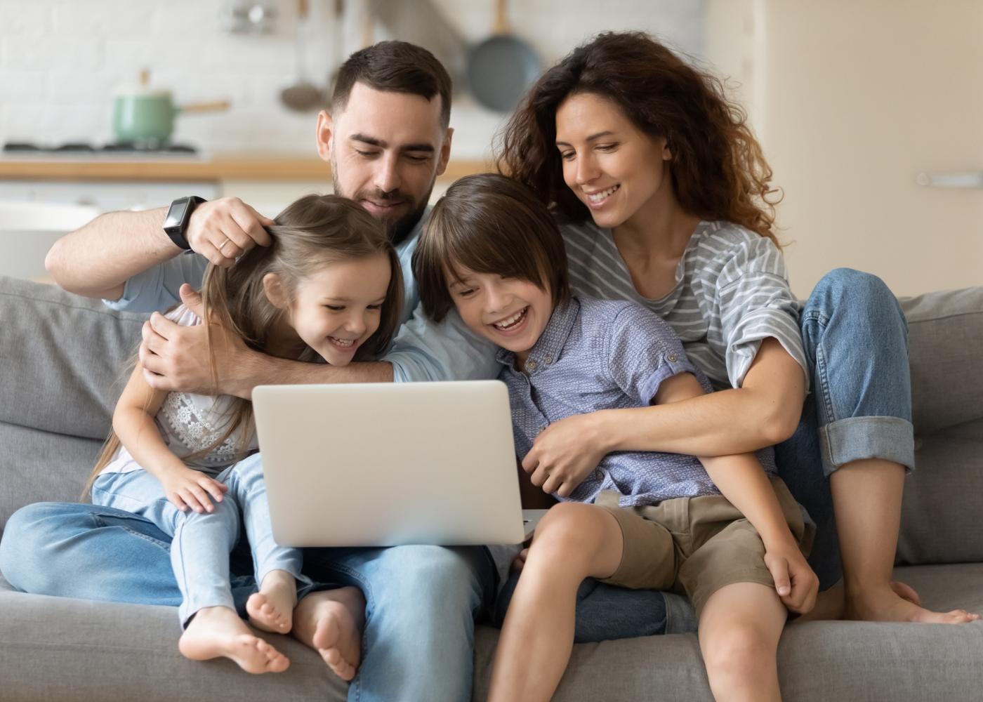 Jovem casal e filhos sentados no sofá em casa