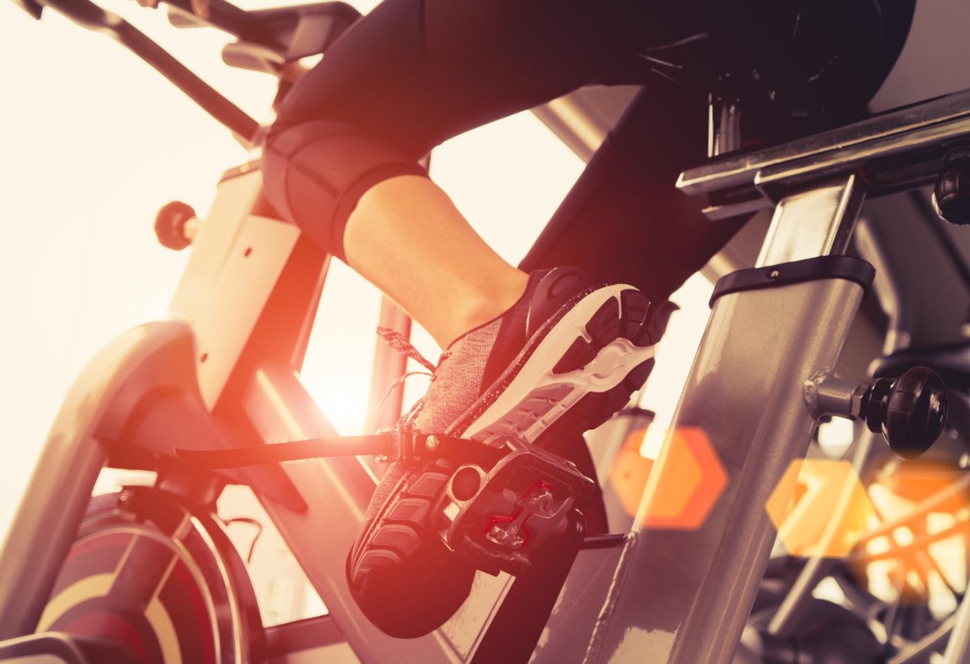 Mulher a fazer bicicleta no ginásio