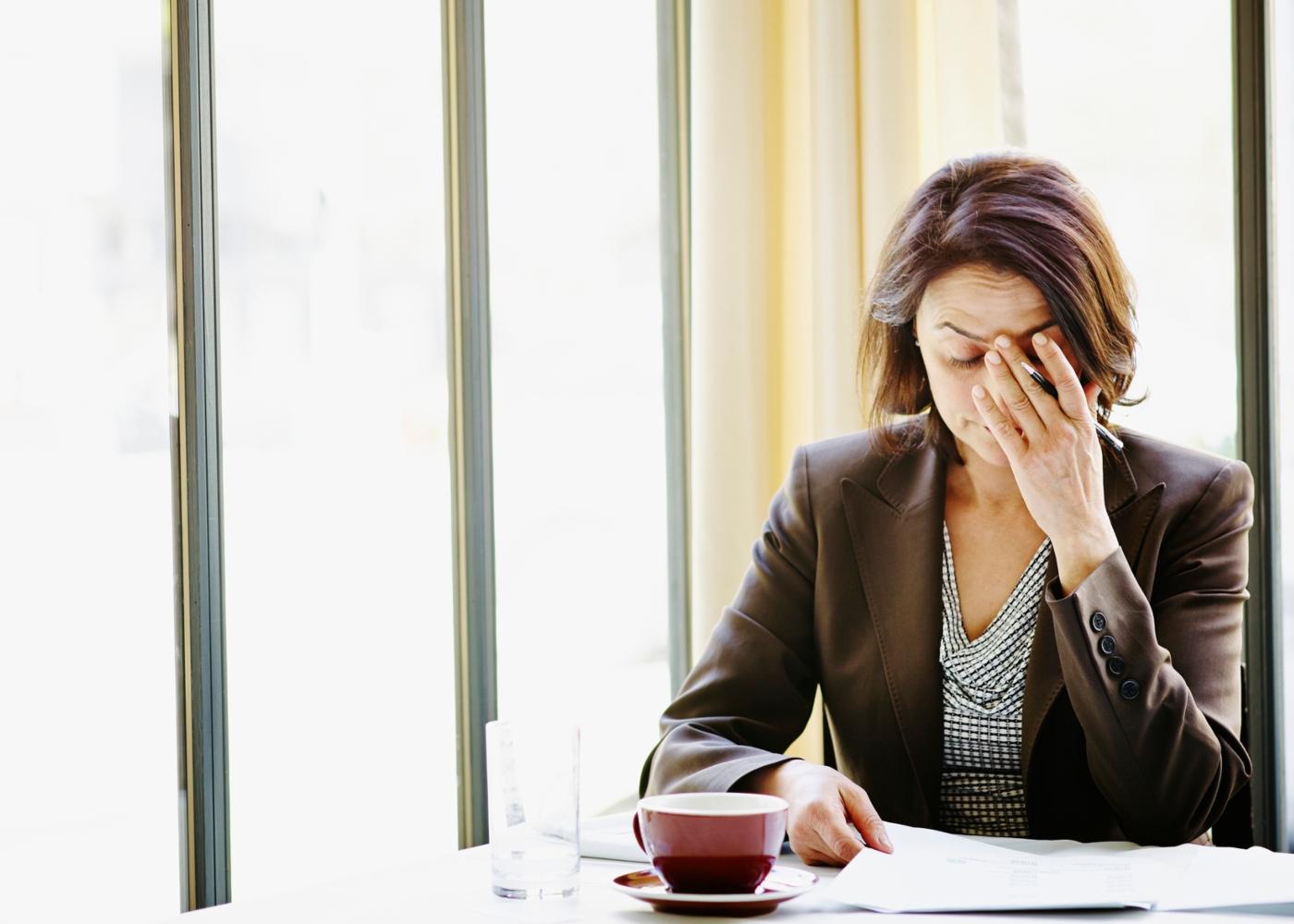 Sintomas da ansiedade: mulher preocupada com o trabalho