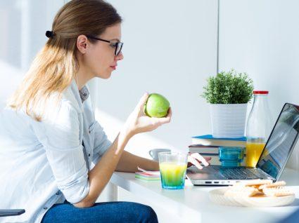 Stress engorda: mulher a trabalhar enquanto petisca