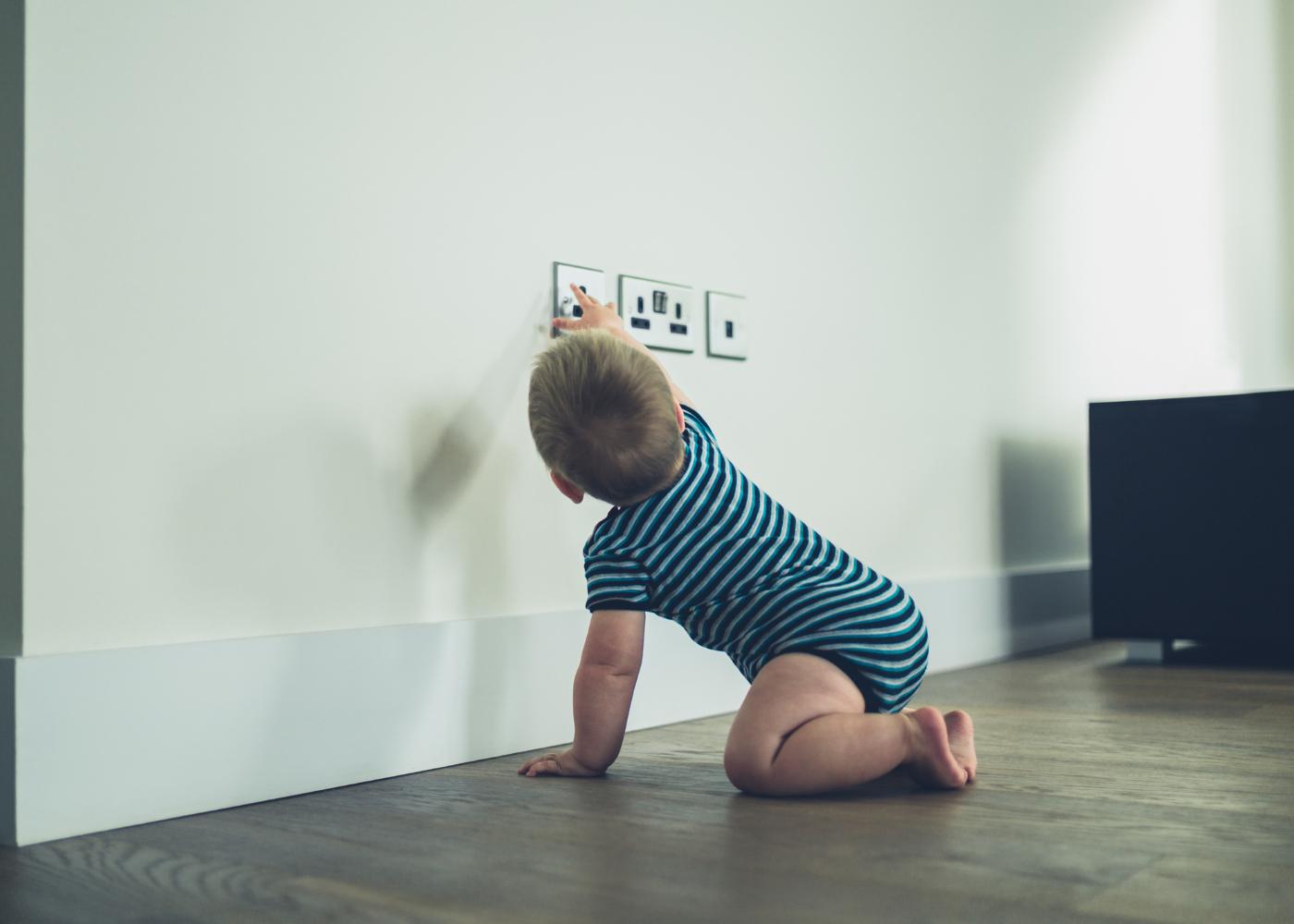 bebé a tentar tocar na tomada