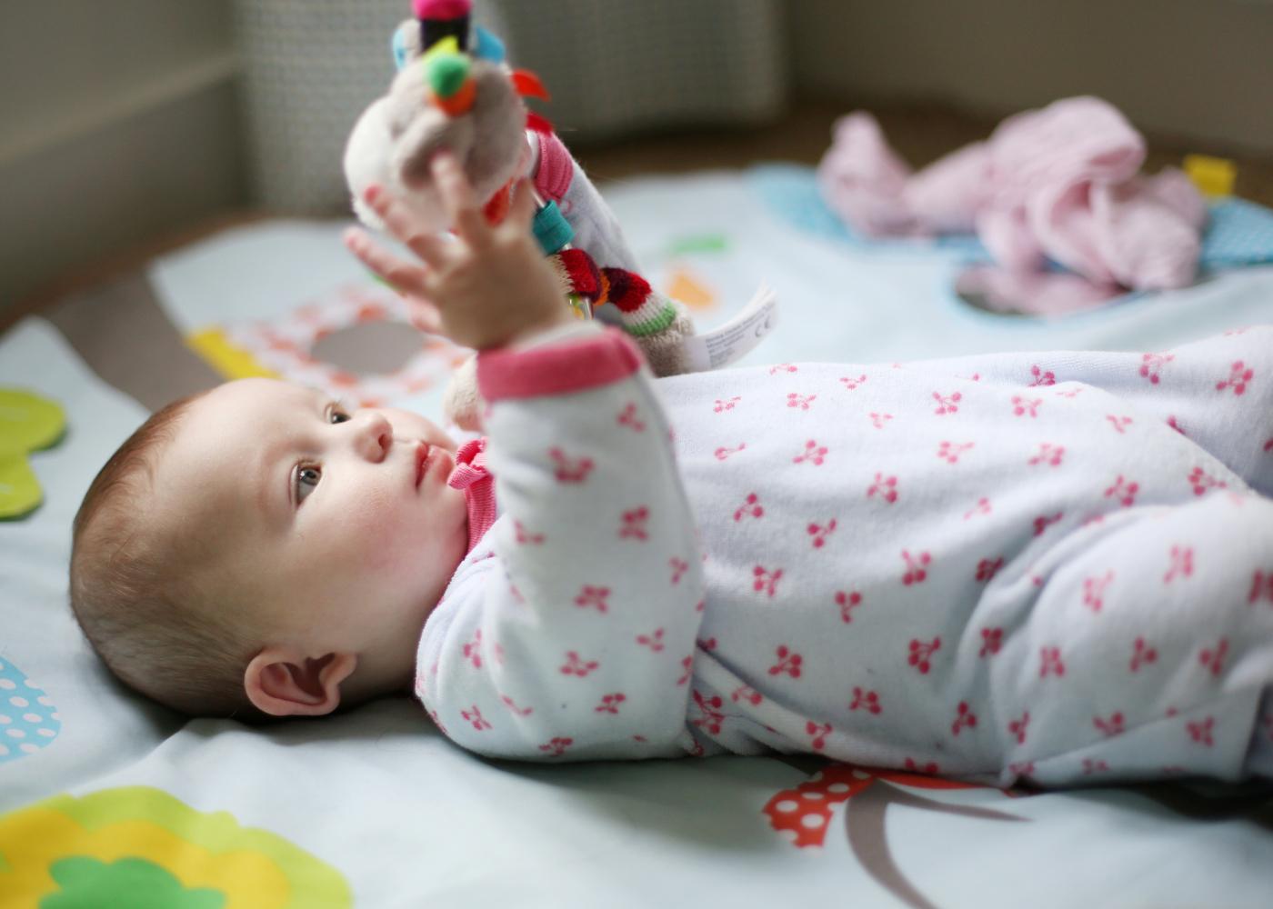 bebé com brinquedo na mão