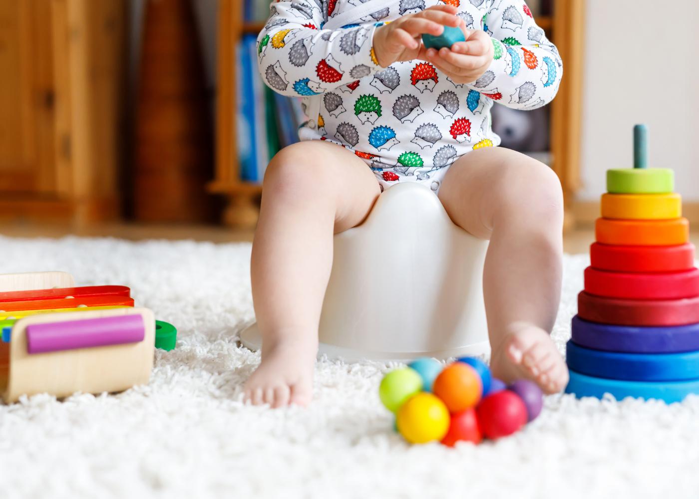 bebé no penico com brinquedos
