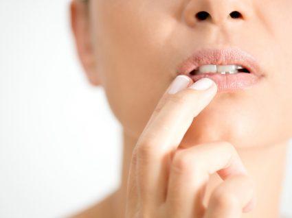 Mulher a aplicar tratamento caseiro para o herpes labial