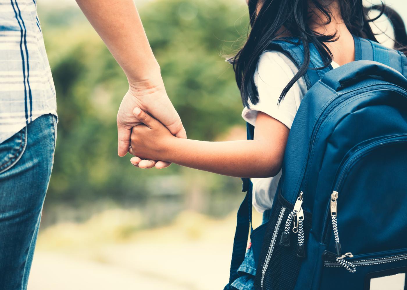 menina a ir para a escola de mão dada com a mãe