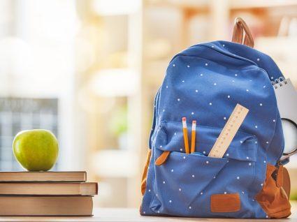 mochila em cima da secretária com livros e maçã