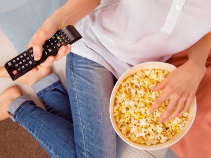 O que petiscar enquanto vê TV: mulher a comer pipocas