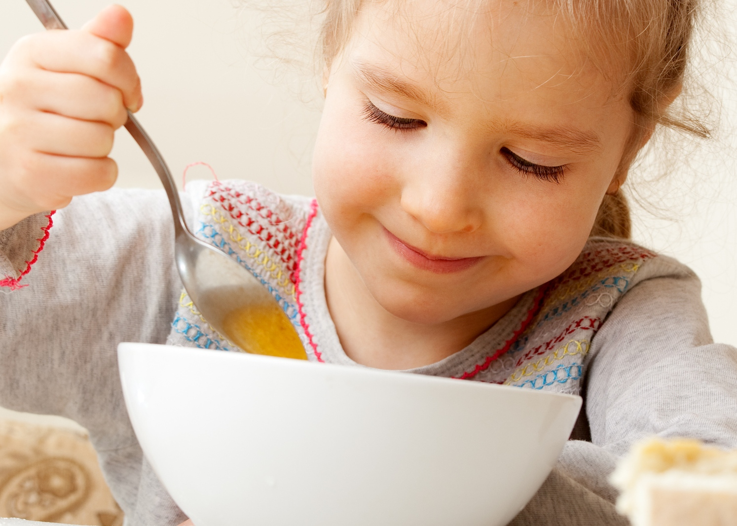 Truques para ajudar as crianças a gostar de sopa: menina a comer sopa