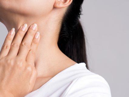 Doenças da tiroide: mulher a fazer apalpação da tiroide