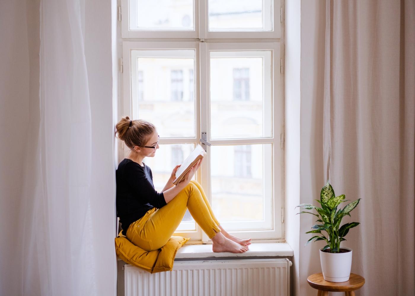 Adolescente a ler um livro no parapeito da janela