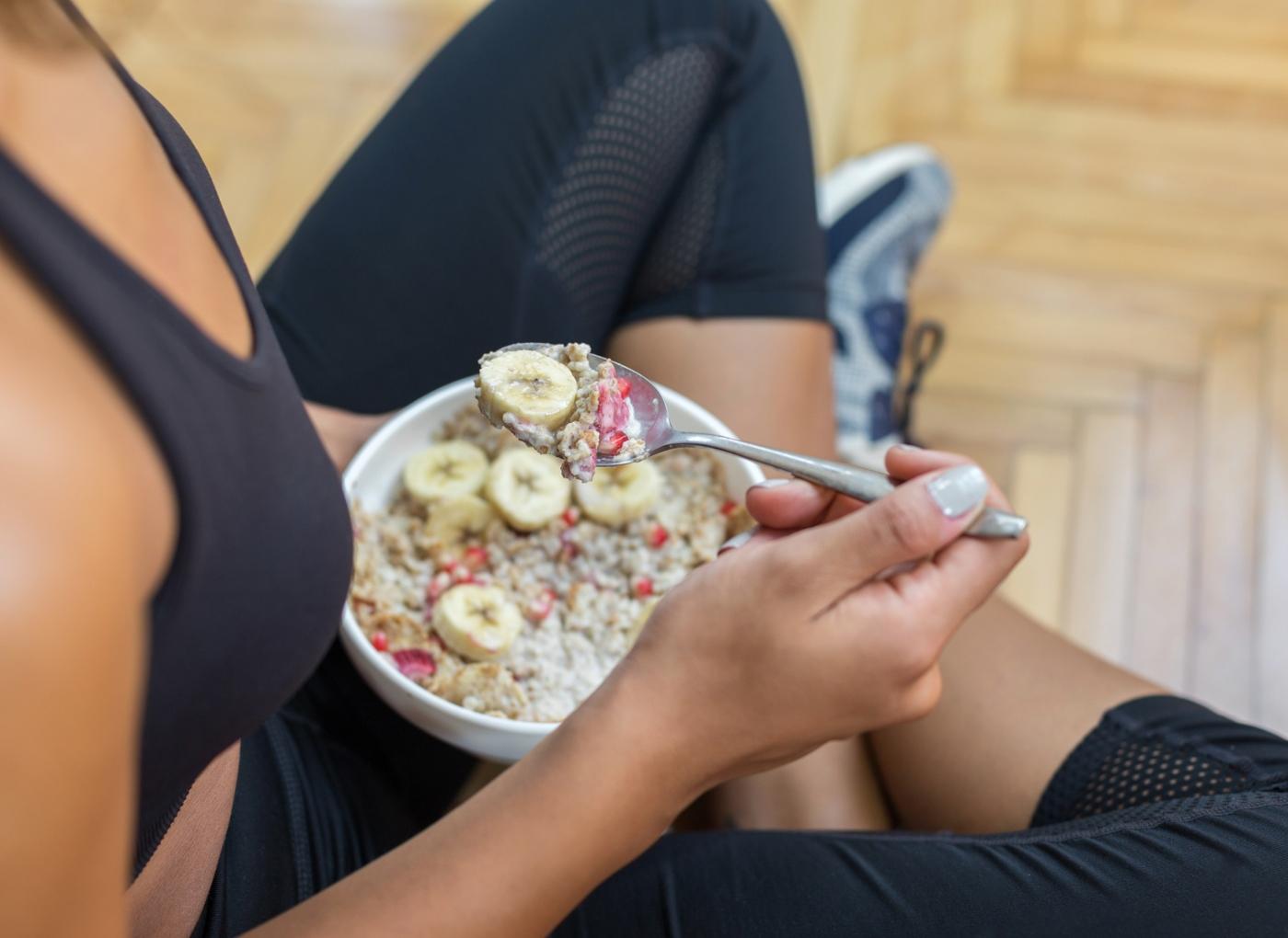 Mulher a comer fruta e cereais depois do treino
