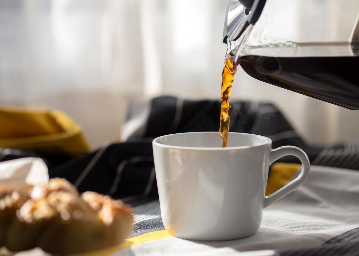 Mulher a encher chávena de café da cafeteira