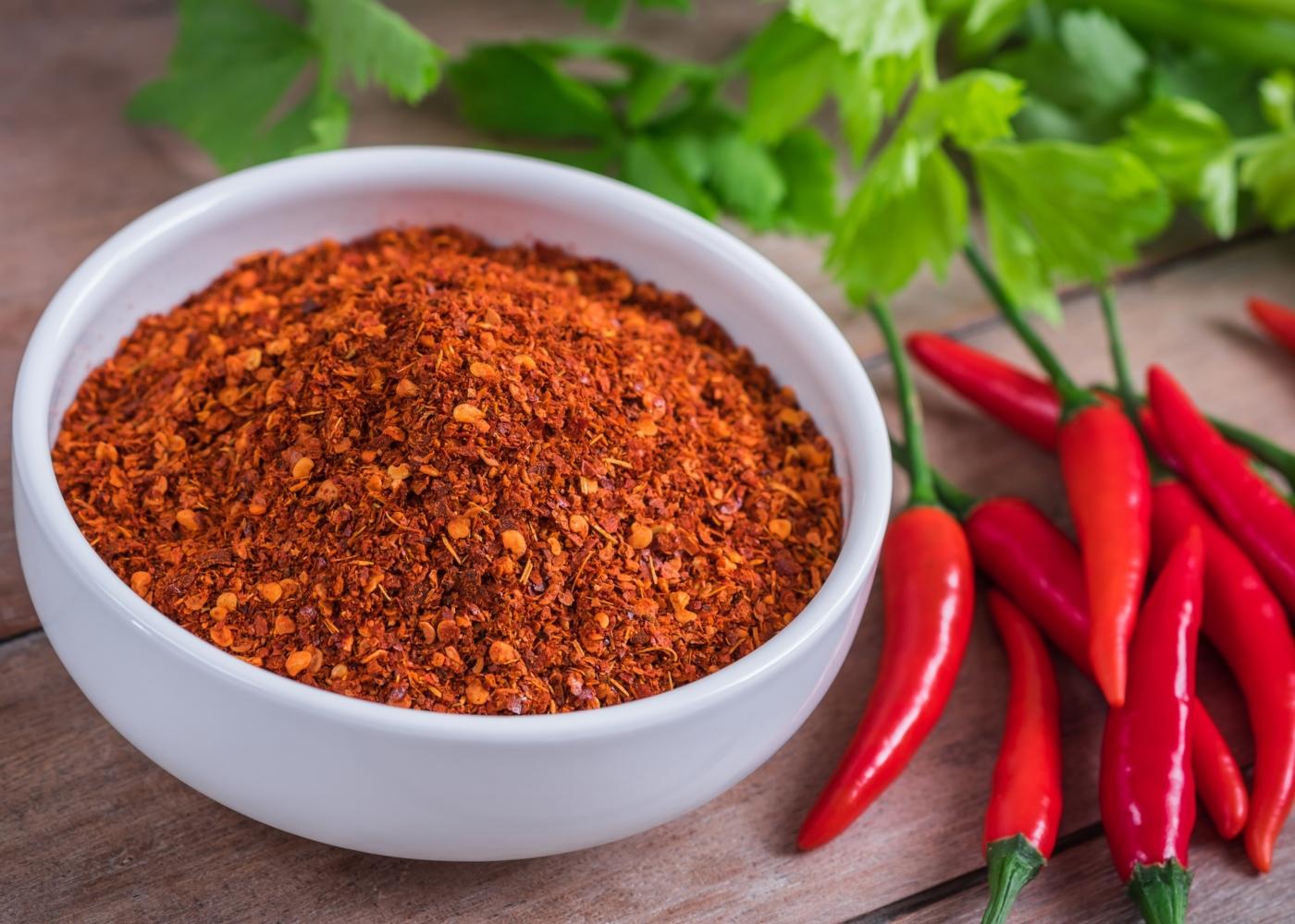 Alimentos termogénicos: taça com pimenta cayenne em pó e em malagueta