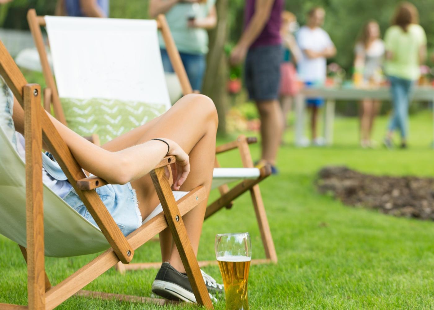 Teenager a beber cerveja sentada no jardim