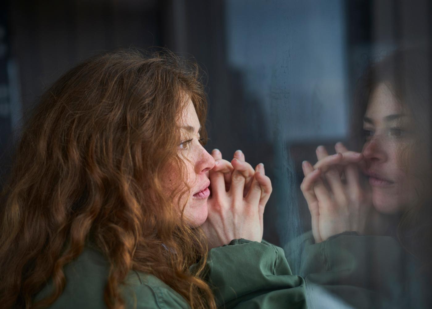 mulher a olhar pela janela a pensar