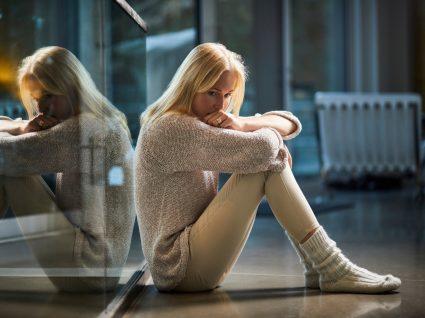 mulher sentada no chão a pensar
