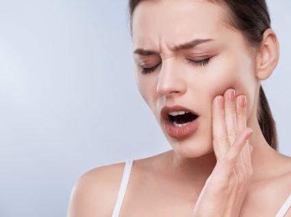 Mulher a pensar no que pode comer para aliviar a extração de dente