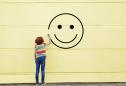 Pessimismo: jovem a desenhar um smile na parede