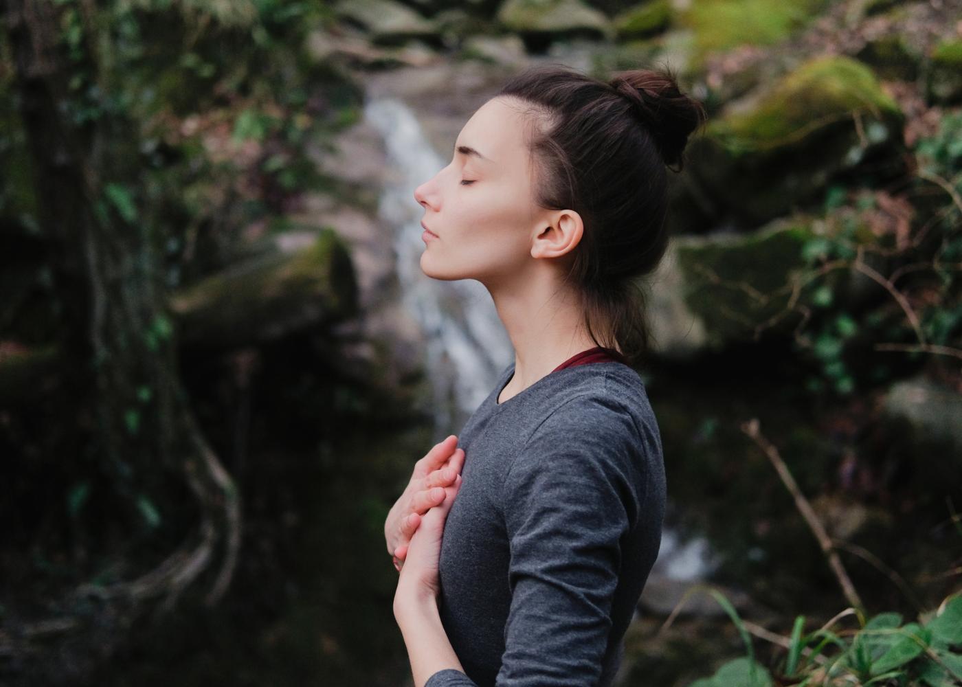 Mulher de olhos fechados a meditar