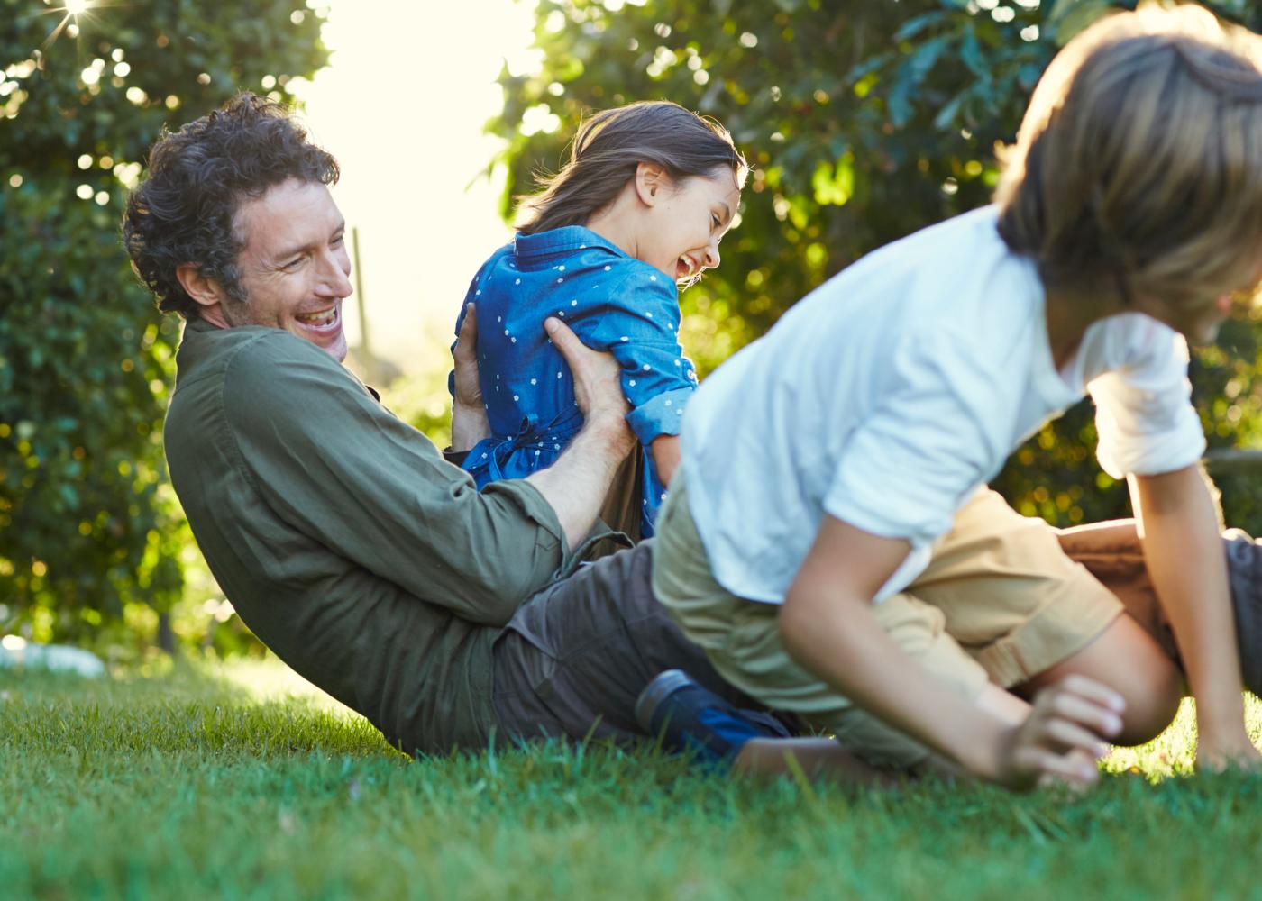 Slow parenting: pai a brincar com os filhos no jardim