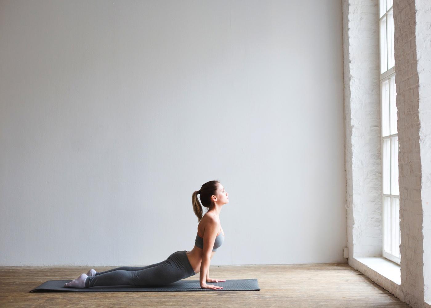 Mulher a fazer alongamentos matinais: postura da cobra