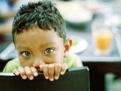 Como lidar com a mentira: menino envergonhado sentado à mesa