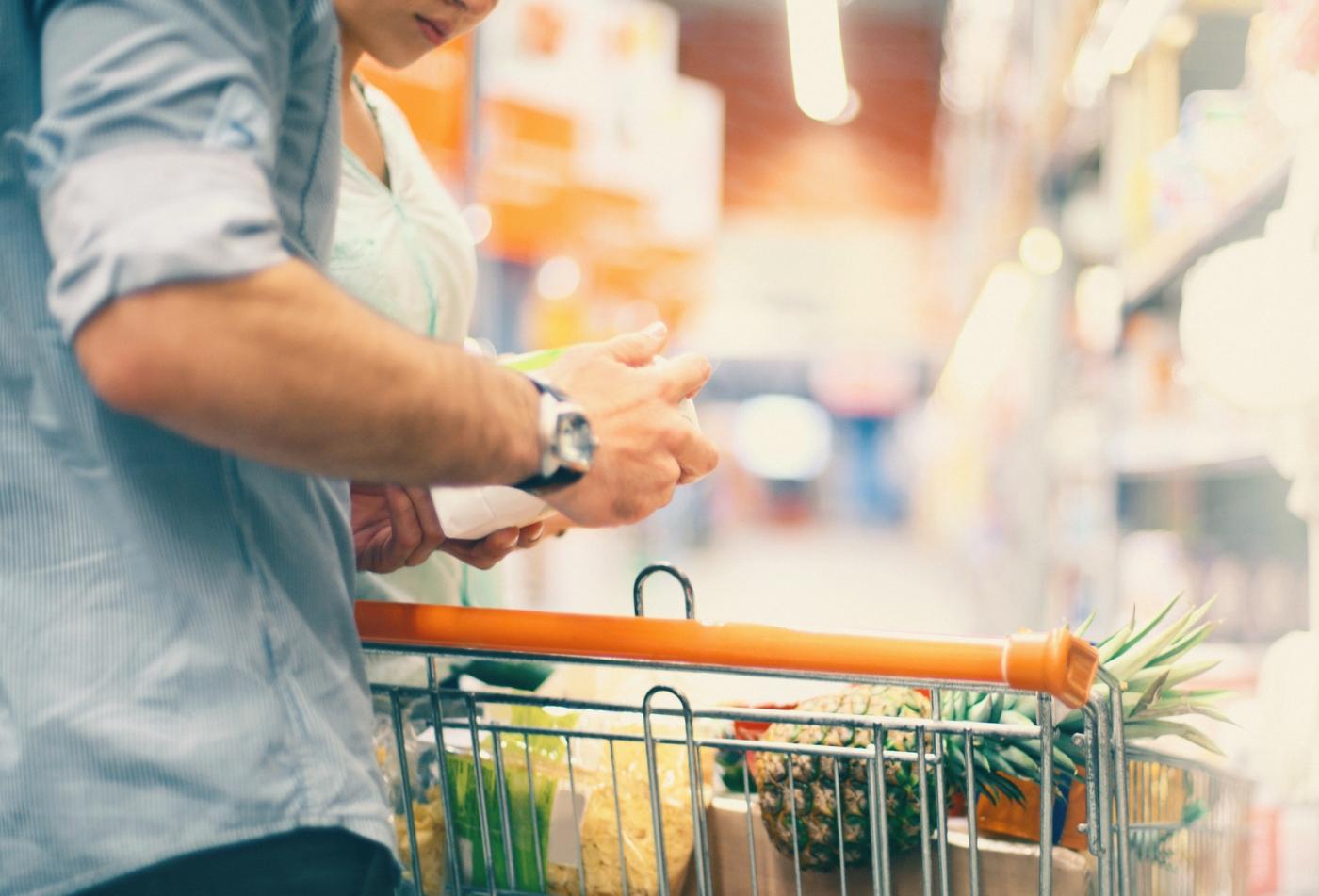 Casal a ler rótulos de alimentos par verificar diferentes formas de açucar nos alimentos