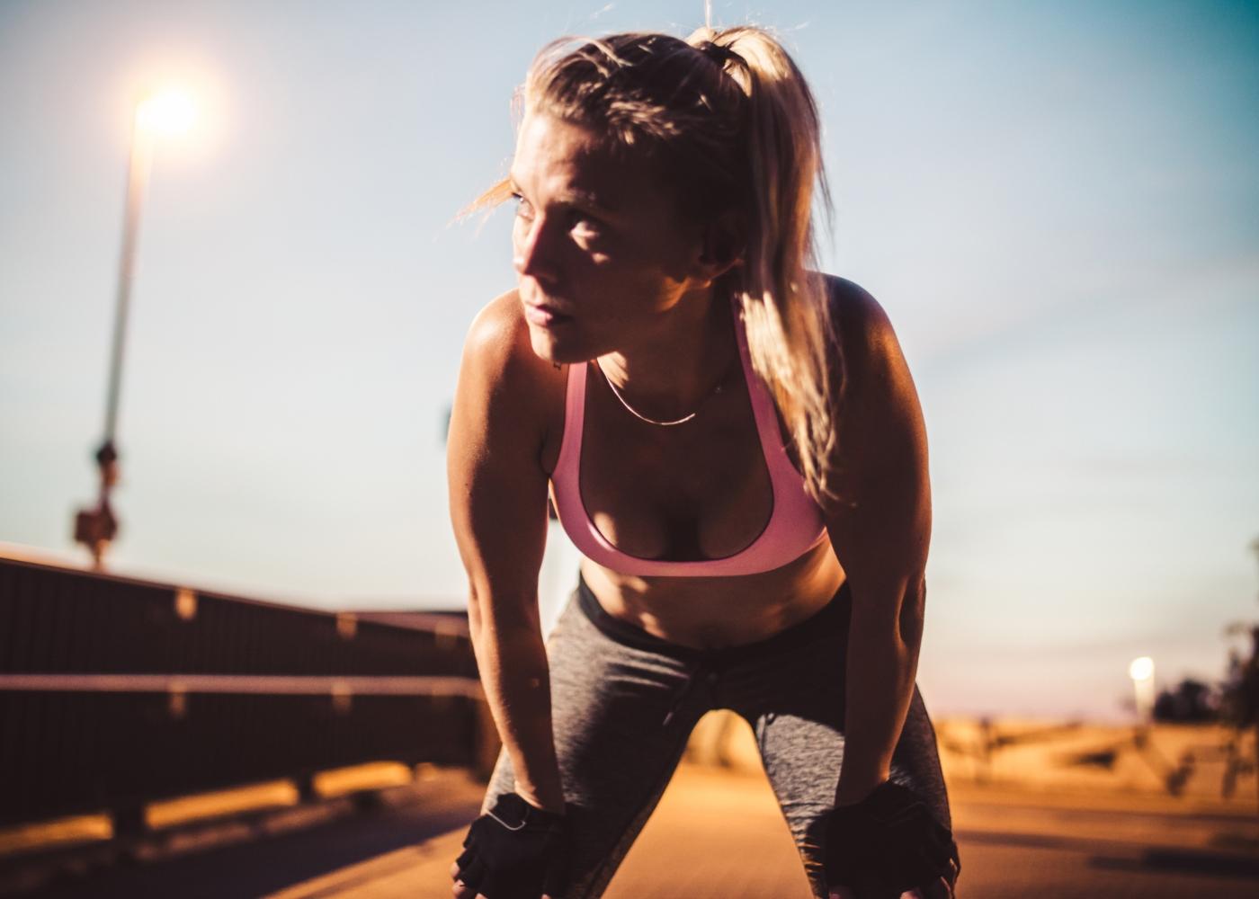 Mulher a recuperar fôlego após treino