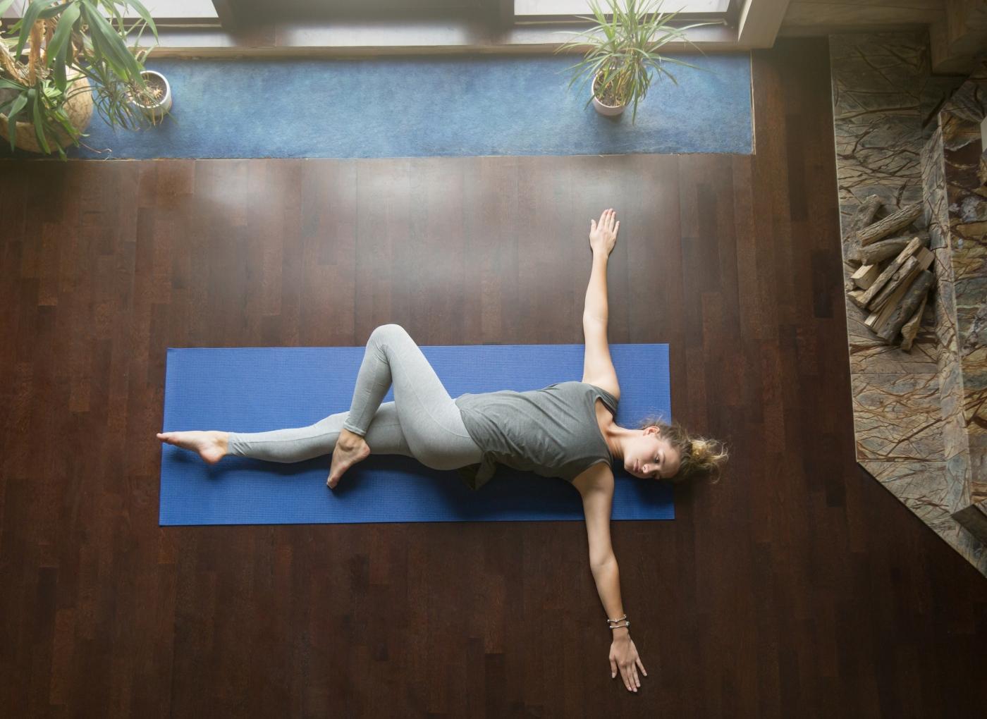 Mulher a fazer alongamentos matinais: rotação alternada do quadril