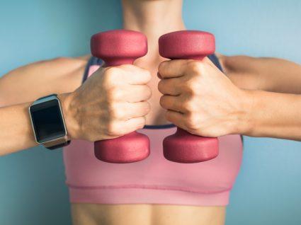 Como aumentar o metabolismo: mulher com pesos nas mãos