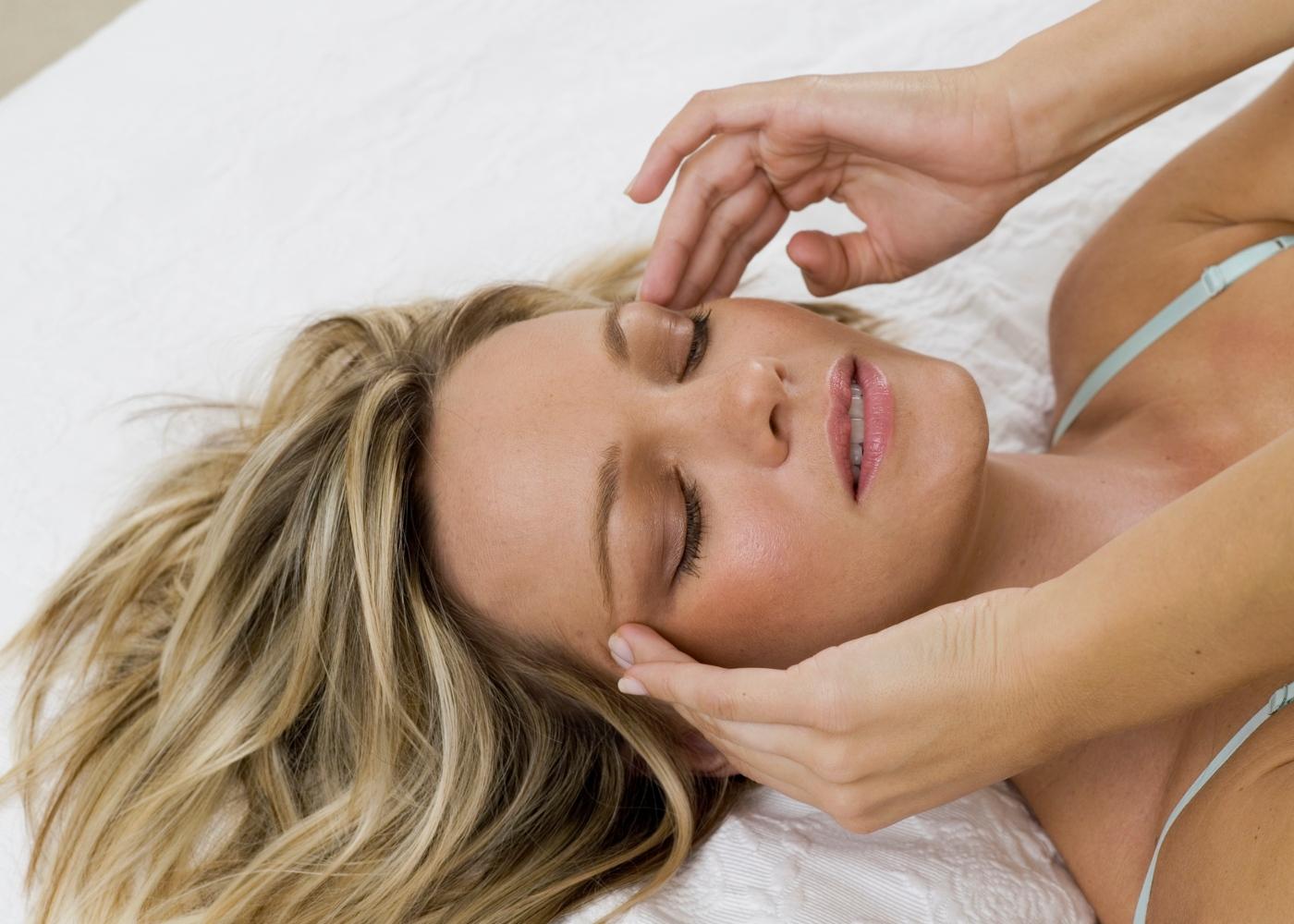 Mulher deitada com dor de cabeça