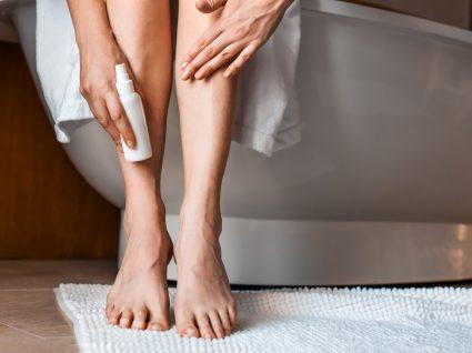 Mulher a passar creme nas varizes das pernas
