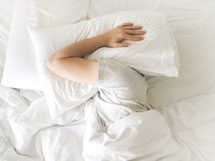 Consequências da falta de descanso: homem deitado na cama