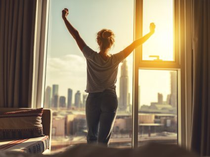 mulher na janela de casa feliz