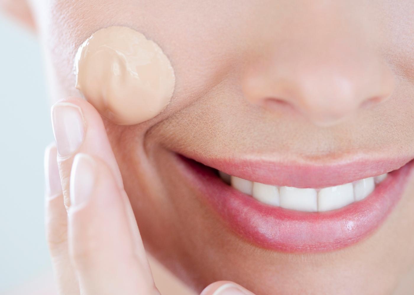 Pele oleosa: mulher a aplicar base no rosto
