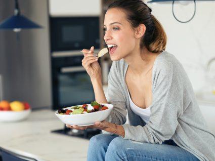 Porque estou sempre com fome: mulher a petiscar em casa
