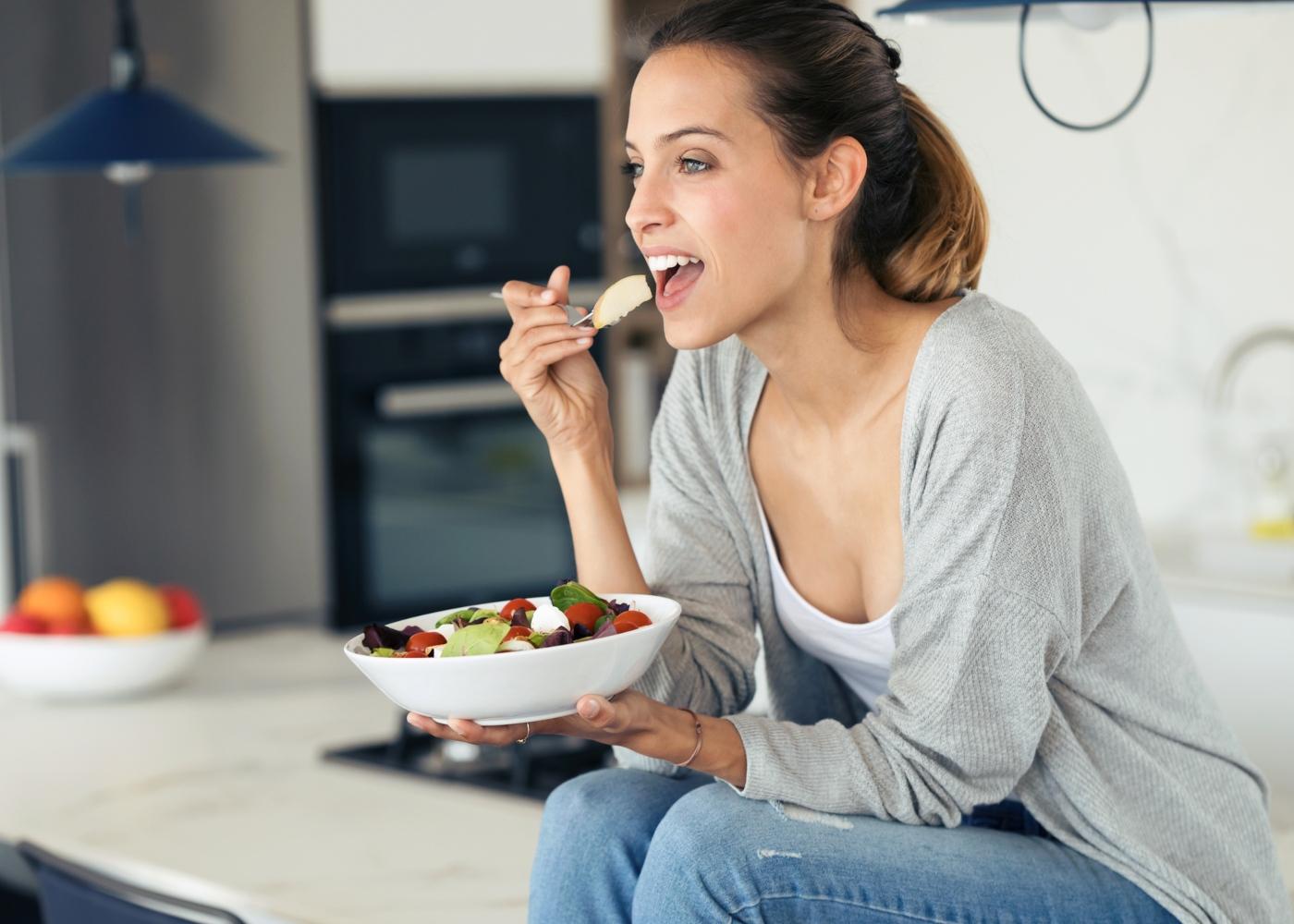 Mulher a comer salada sentada na bancada da cozinha