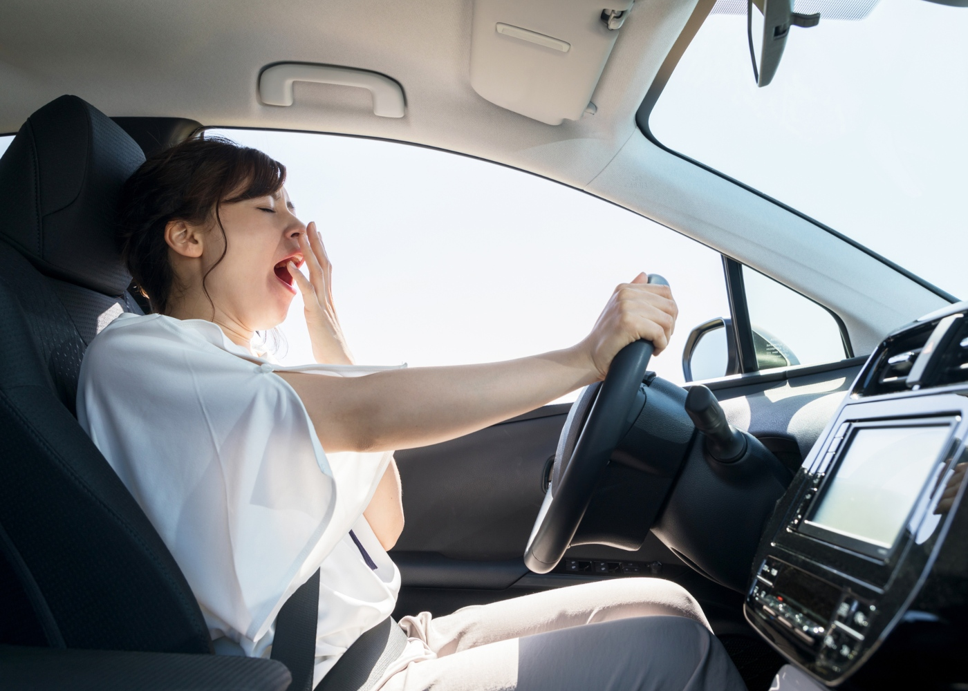 Consequências da falta de descanso: mulher a conduzir com sono
